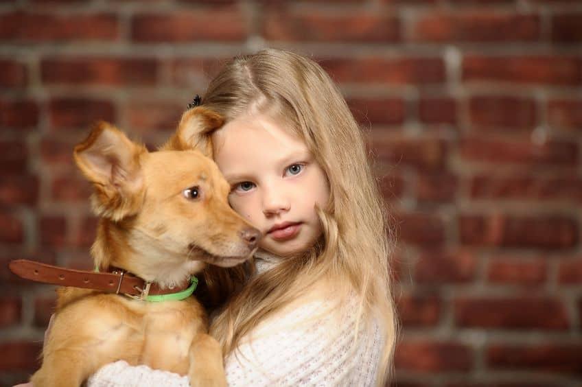 Imagem de menina abraçando cachorro.