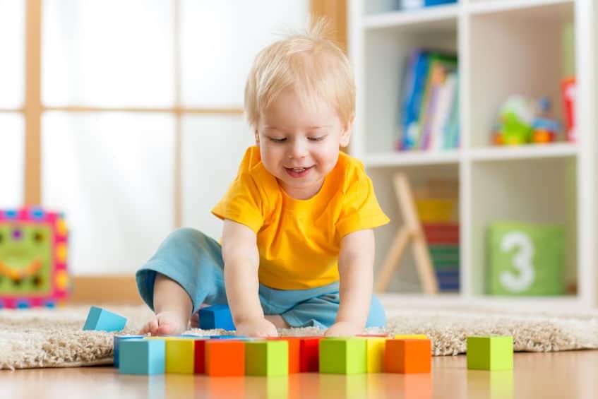 Imagem de criança brincando com brinquedos no chão.