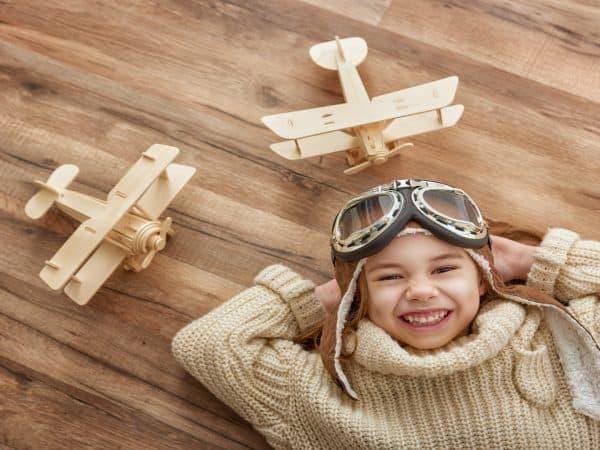 Imagem com menino deitado com aviões de madeira ao lado.