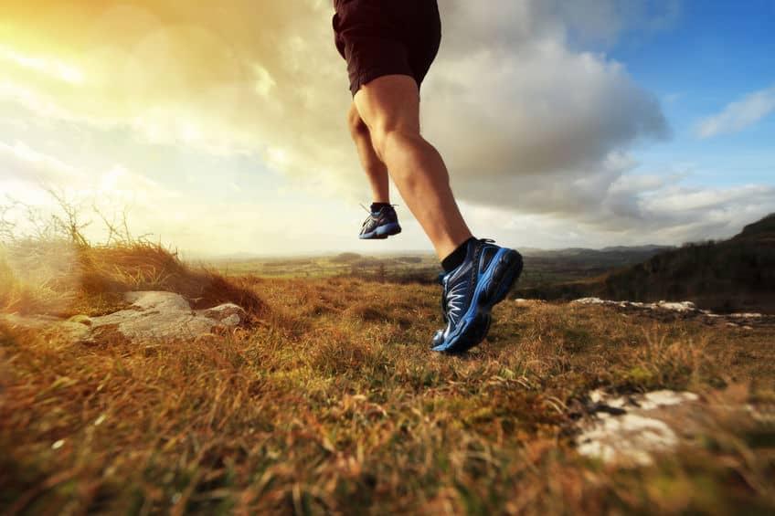 Imagem mostra pernas de um corredor e tênis de corrida em contato com a grama