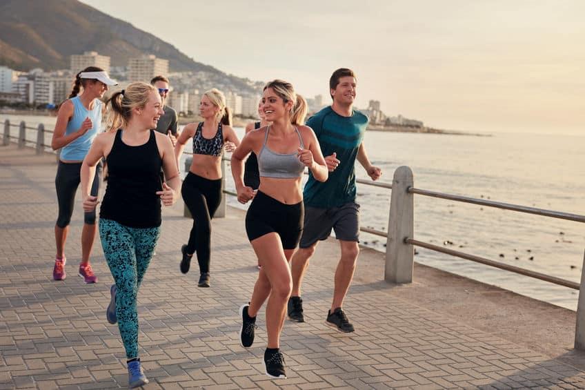 Grupo de pessoas correndo em um calçadão à beira-mar