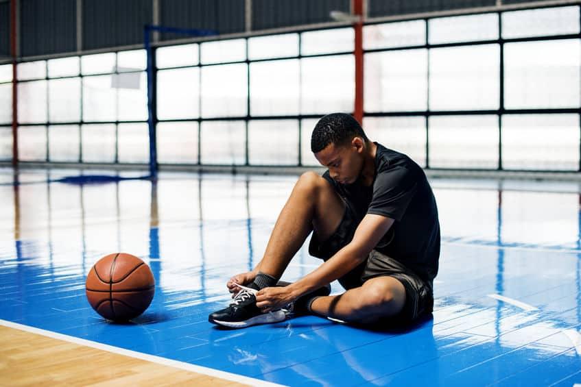 Imagem de atleta sentado na quadra de basquete amarrando seu tênis com a bola ao lado.