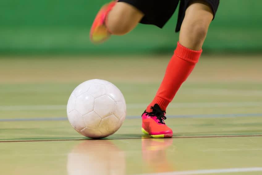 Imagem de pessoa chutando bola em jogo de futsal.