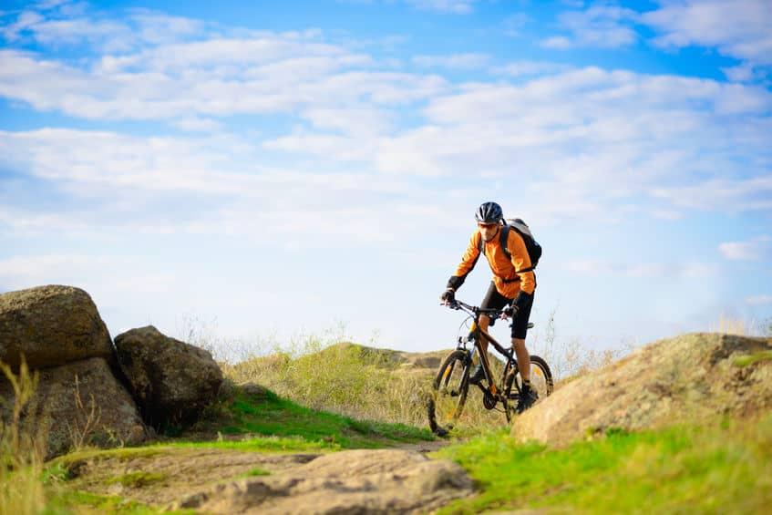 Ciclista com sua bicicleta em meio a montanhas.