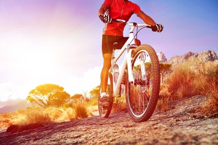 Ciclista andando de bicicleta branca em montanhas.