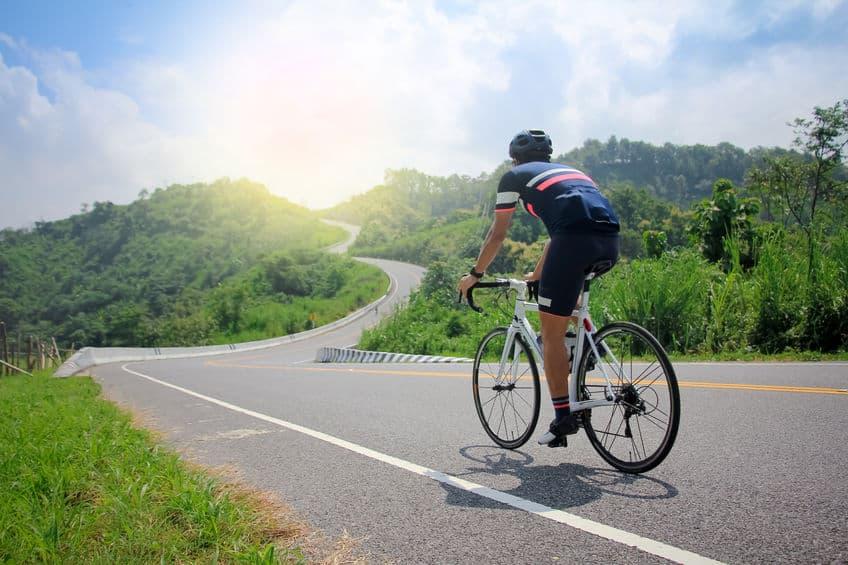 Imagem de ciclista pedalando em meio a natureza.