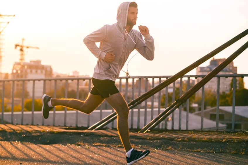 Homem correndo com por do sol ao fundo.