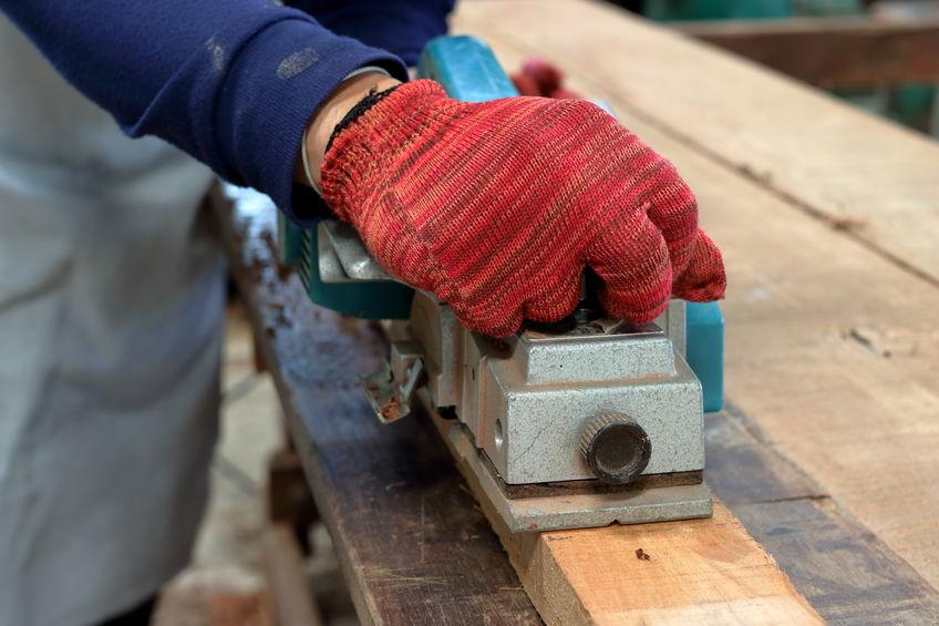 Hombre cepillando madera