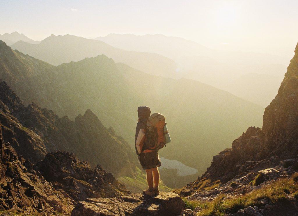 menino na frente das montanhas