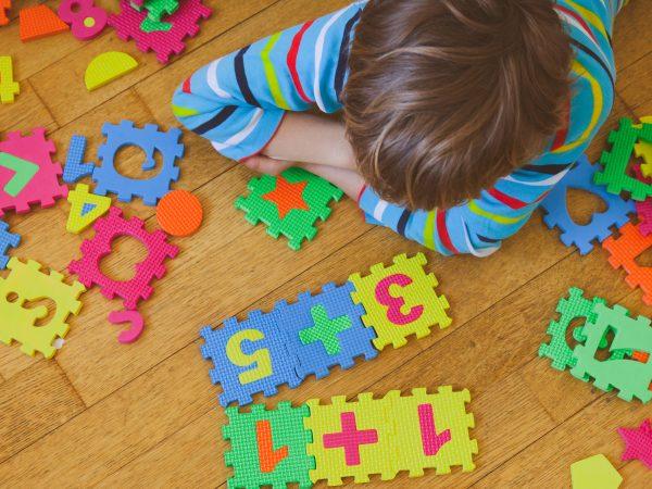 criança fazendo um quebra-cabeça