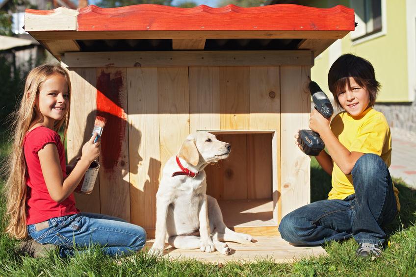 Duas crianças brincando com seu cachorro na casinha de cachorro