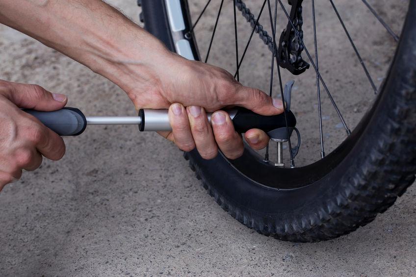 O jovem infla a roda de bicicleta