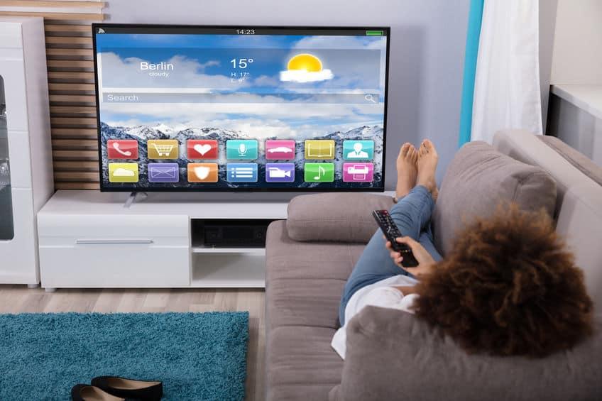 woman watching tv on sofa
