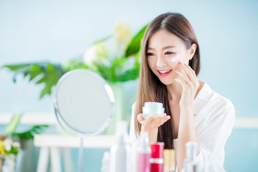 menina asiática usando um creme anti-idade