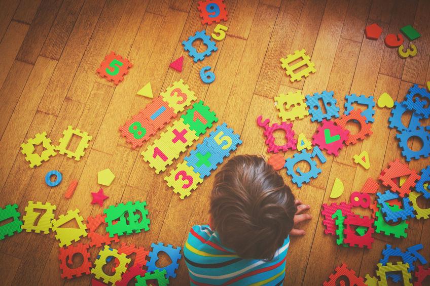 garotinho brincando com brinquedos de matemática