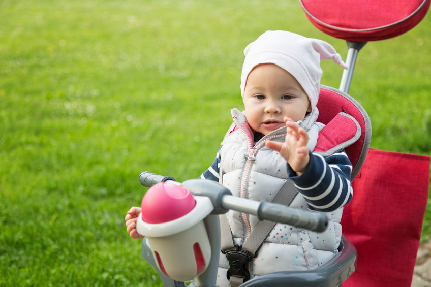 One year old baby girl sitting in a red and grey tricycle