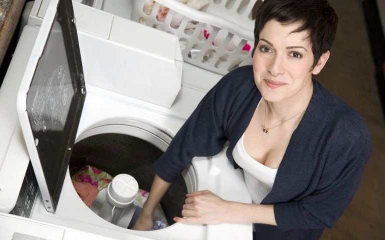 woman putting clothes inside the washing machine