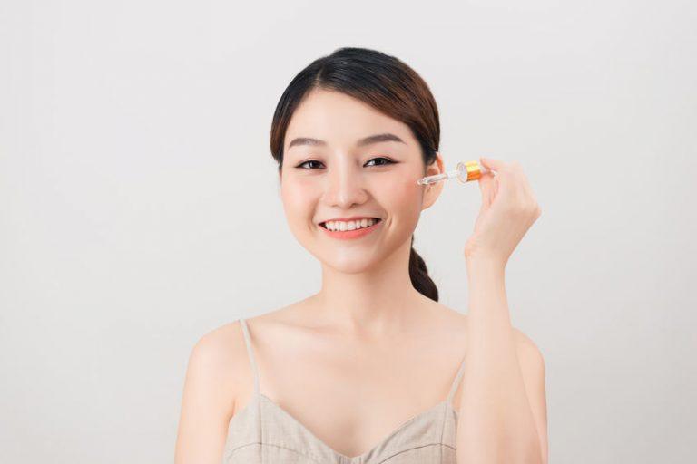girl applying serum on her face