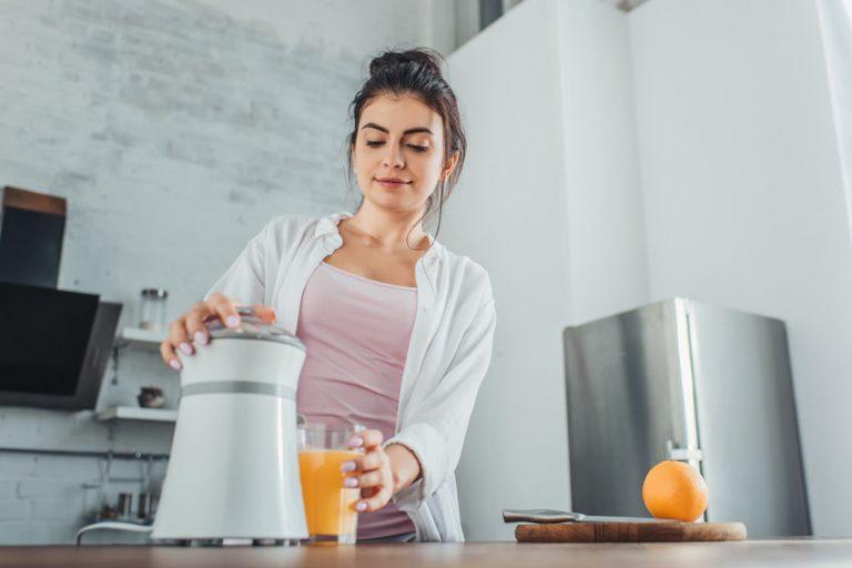 Girl using a fruit juicer