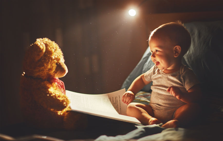 Happy baby reading a book with teddy bear in bed