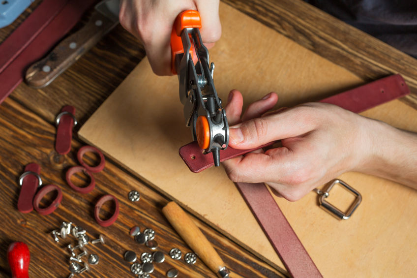 Master holding a hole punch and a piece of leather. On brown wooden table scattered with tools and accessories.