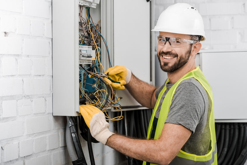 smiling electrician repairing electrical box with pliers in corridor and looking at camera
