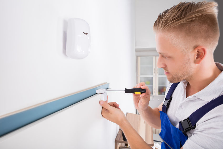 Man Installing Security System Door Sensor