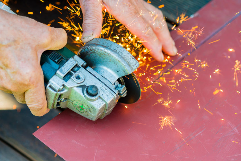 Close-up of worker cutting metal with grinder. Sparks while grinding iron