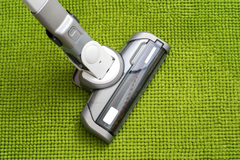 vacuuming a green carpet