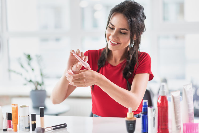 Cheerful young woman squeezing cream base on arm skin