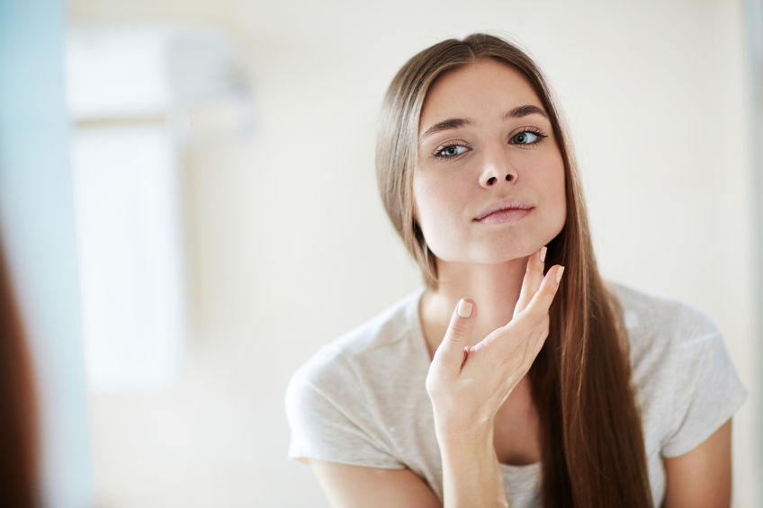 young girl applying some cream in the face