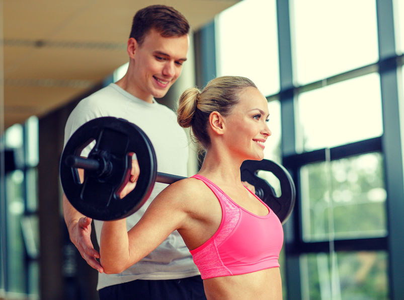 smiling man and woman with barbell in gym