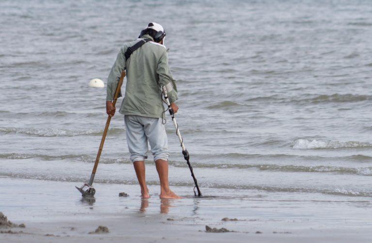 Homem perto do mar com um detector de metal