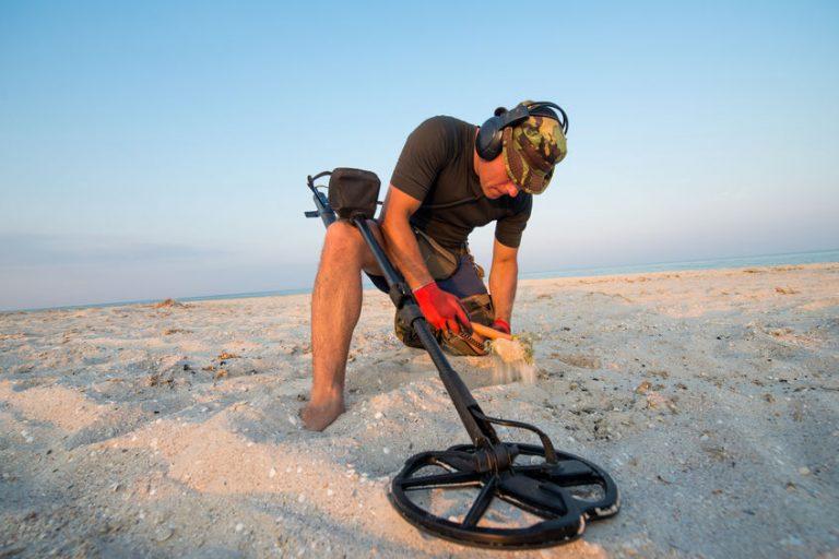Homem na praia com um detector de metal