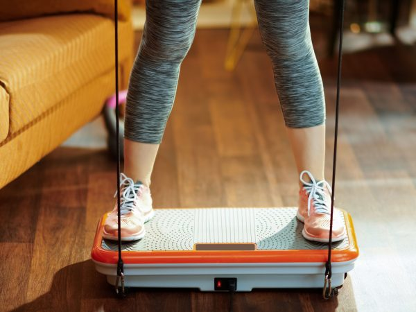 Closeup on fit sports woman in fitness clothes at modern home training using vibration power plate.