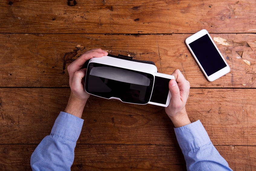 Hands of man holding virtual reality goggles and smartphone