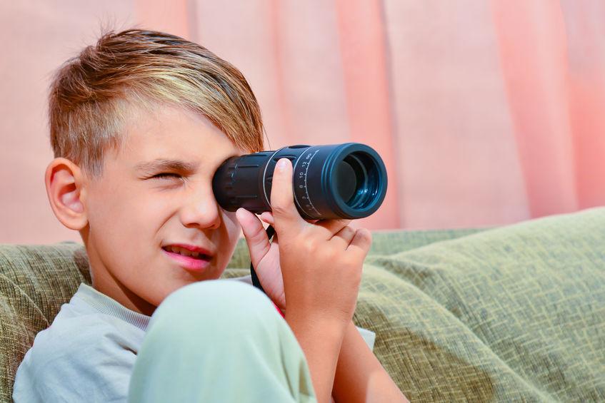 garoto usando uma luneta