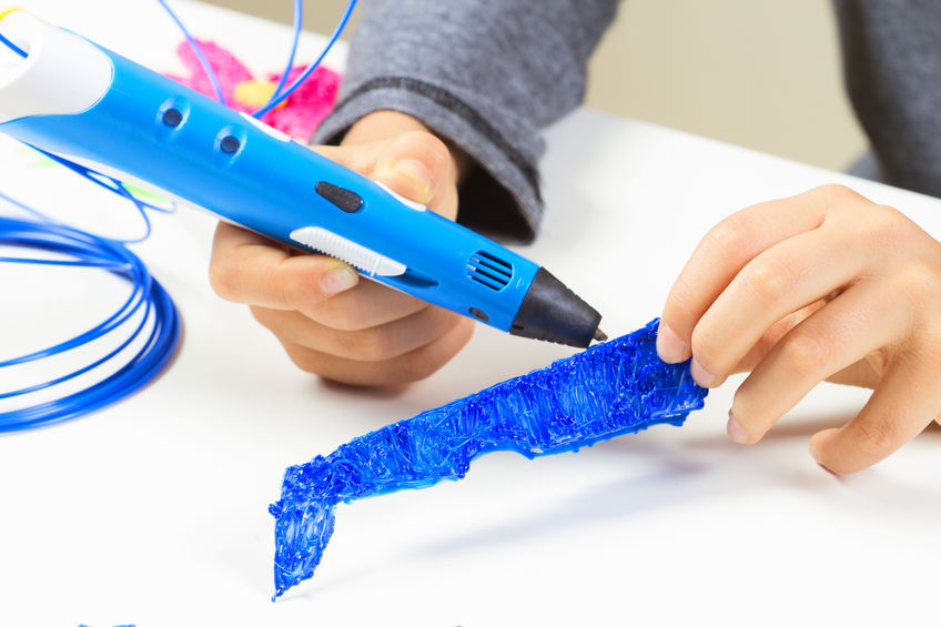 Kid's hands creating with 3d printing pen.