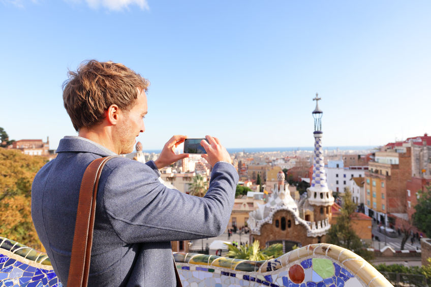Tourist man taking photo in with smartphone in park guell, barcelona, spain. young professional business man sightseeing taking picture with smart phone in spain,