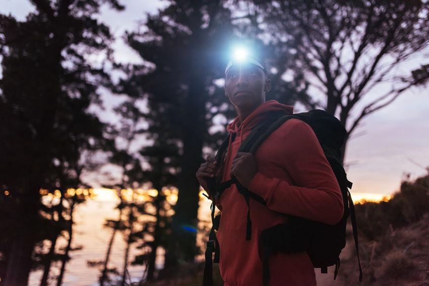 menino andando à noite com lanterna de cabeça