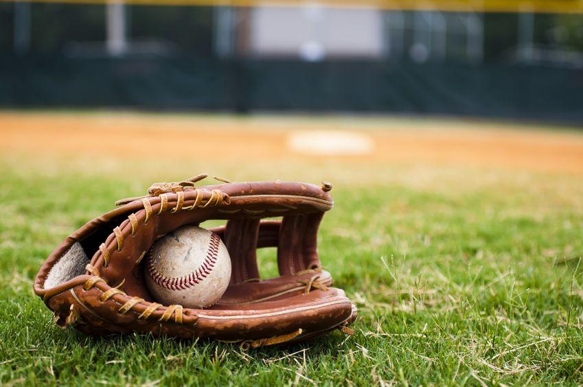 Imagem de luva e bola de beisebol em gramado.