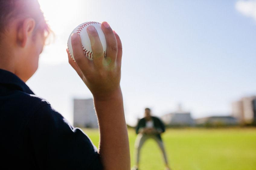 Menino se preparando para arremessar bola.