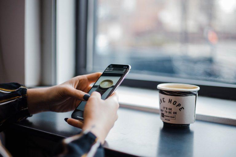 tomando café com celular na mão