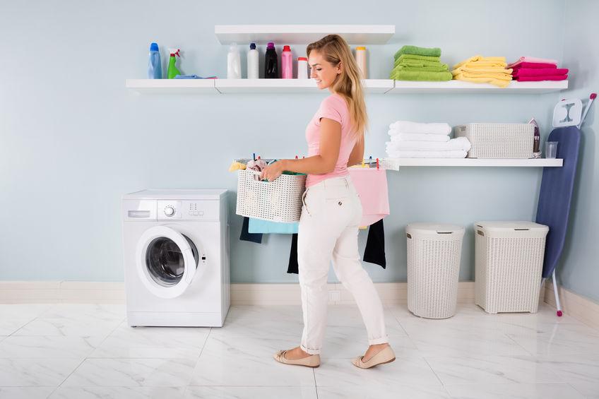 Mulher levando roupas para secadora.