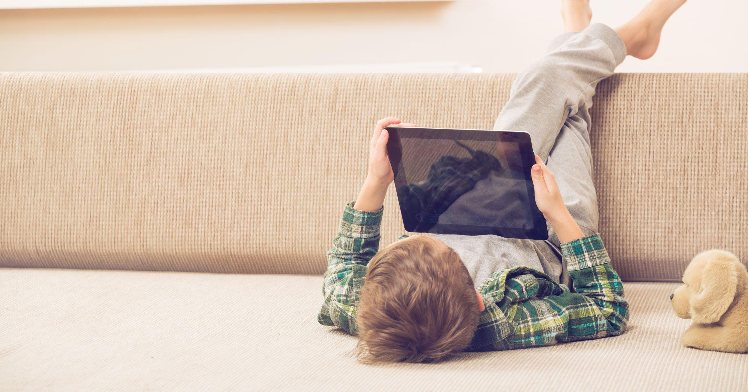 Menino bonitinho brincando com um tablet pc no sofá em casa