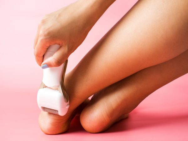 Girl using foot file to clean hard skin. Feet skincare