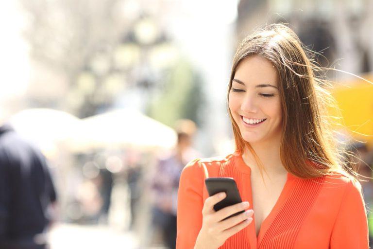 menina sorrindo com o celular dela