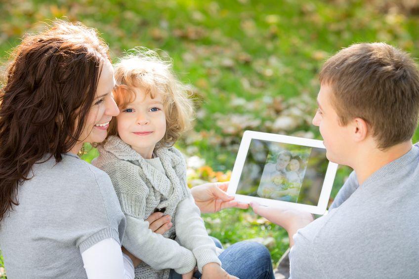 família feliz usando o tablet pc ao ar livre no parque outono