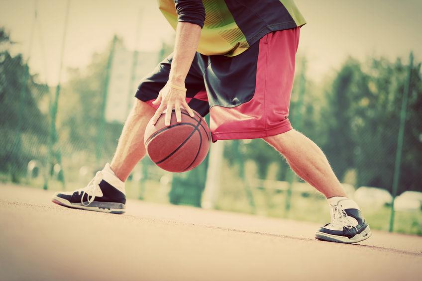 Jovem na quadra de basquete driblando com a bola. Clima vintage