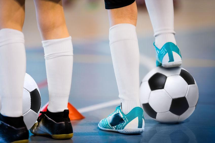 segurando uma bola de futebol com o pé